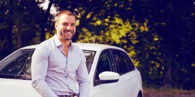 Man smiling in front of his car